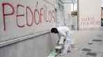 Un pintor comienza a repasar con pintura blanca una de las pintadas aparecidas en rojo esta ma�ana con acusaciones de pedofilia y pederastia en las paredes de la parroquia San Juan Mar�a Vianney de Granada
